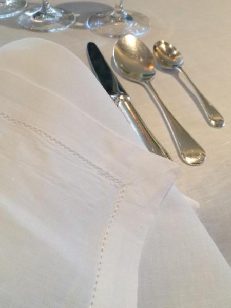Petrus: posate d'argento e tovaglie di lino bianco