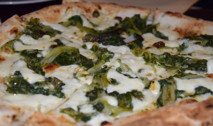 Pizza con provola e scarola saltata con uva passa e pinoli