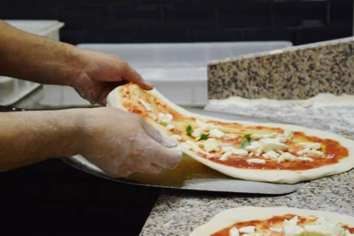 Pizzeria Bella Napoli, un momento della preparazione della pizza