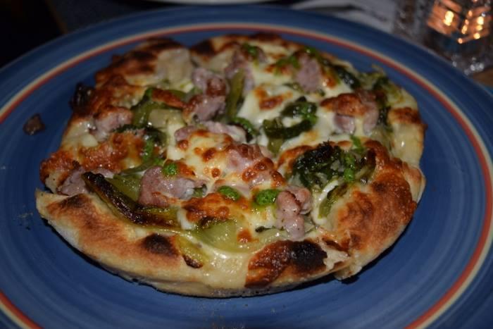 Pizz'ino con scarola saltata, uva passa, pinoli, salsiccia di nero casertano e provola