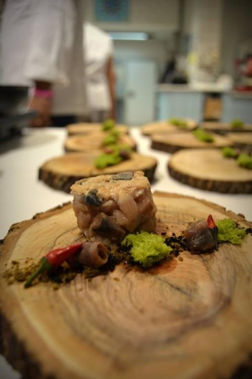 L'ulivo incontra il mare, sgombro marinato e poi scottato, servito con polvere di olive celline su di un piatto di legno d'ulivo