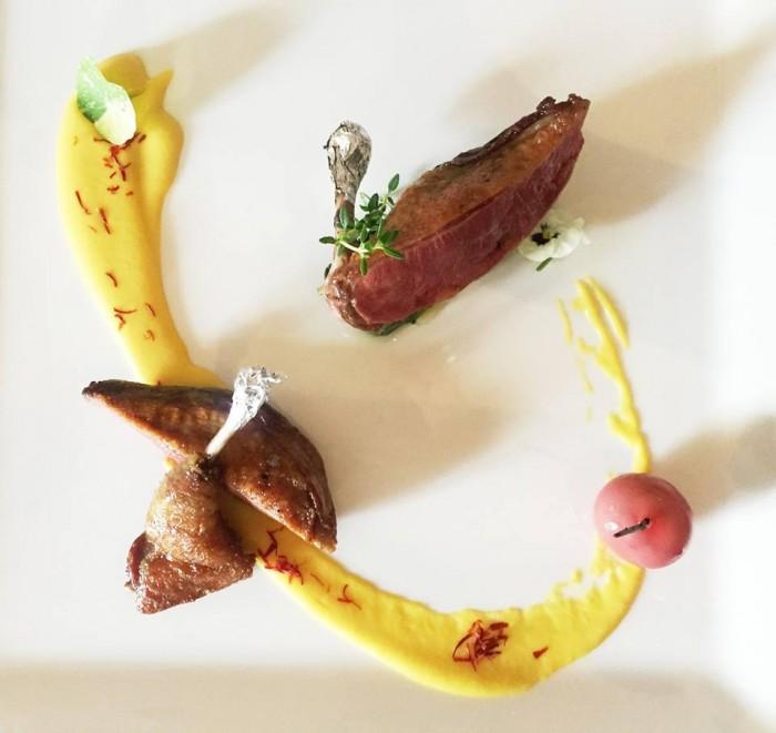 Taverna Estia, coscia e petto di piccione, salsa pannocchia e pistilli di zafferano, cubotto di spinaci e finta ciliegia di cioccolato bianco con composta di ciliegia e cannella