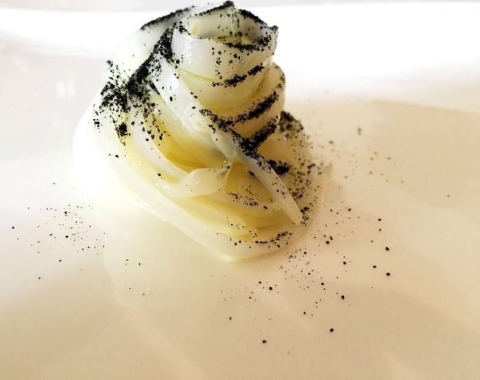 Taverna Estia, finto crudo di calamaro condito con olio sale e limone con nero del calamaro, olive, capperi, pane