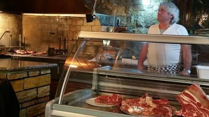 Le Querce, il titolare Attilio affianco all'angolo dedicato alla carne con brace a vista