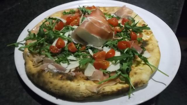 Ristorante Pizzeria Grotta Azzurra Pizza con mozzarella, scaglie di parmigiano, crudo, pomodorini e rucola