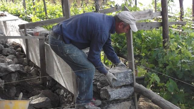 Azienda Marisa Cuomo Operaio intenso a costruire il muretto di contenimento