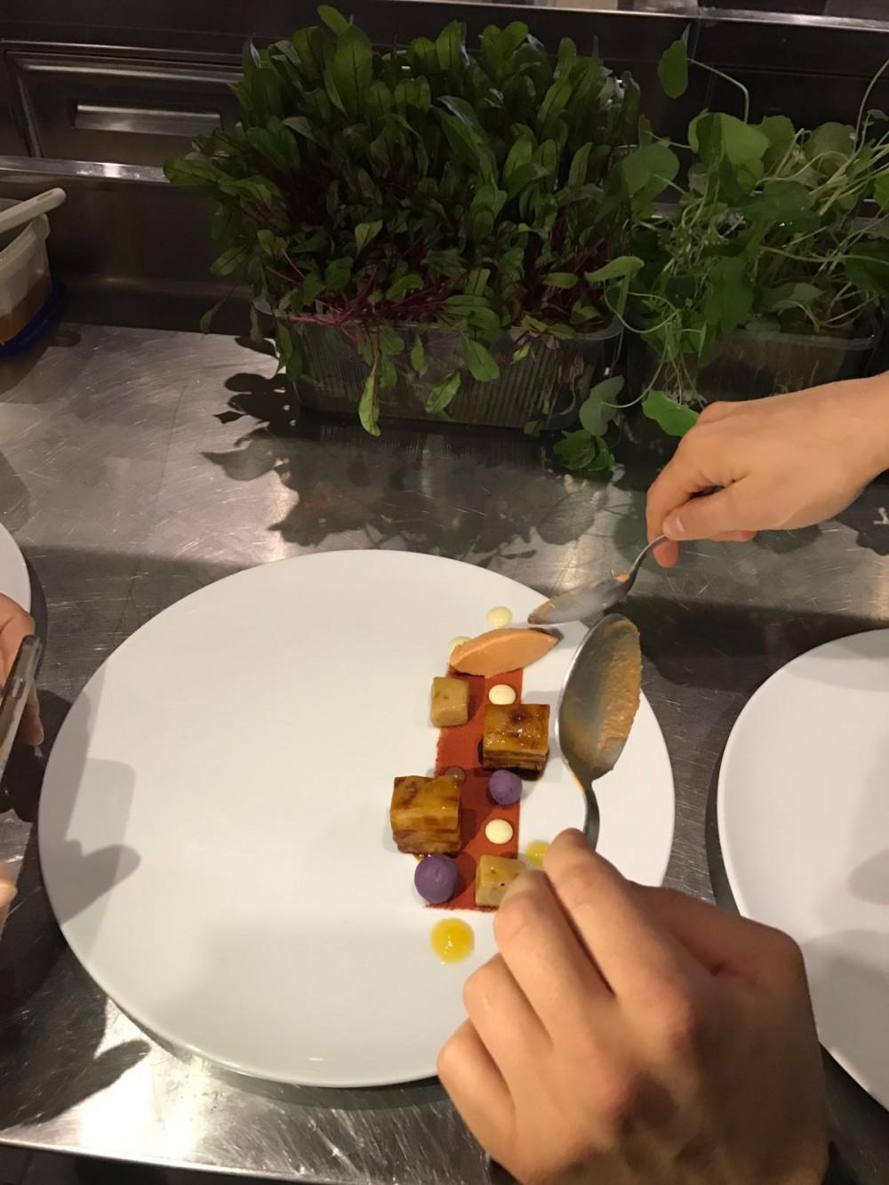 Preparazione del piatto con chenelle di gelato di pomodoro