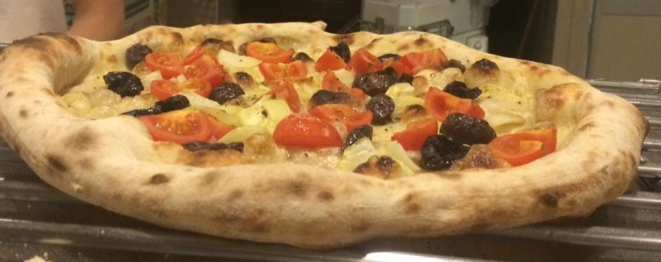 Tonda, pizza in uscita dal forno a legna