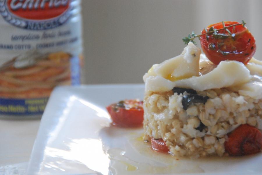 Tortino di grano con olive nere, pomodorini confit al timo e petali di baccala'