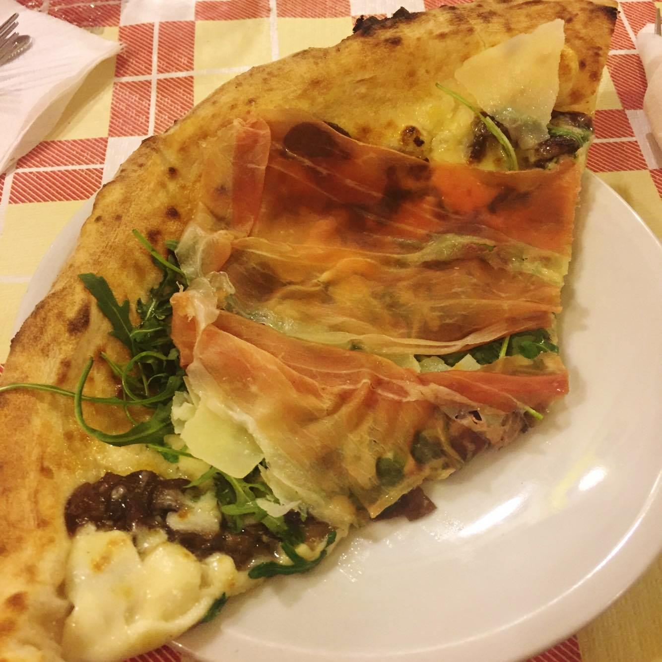 La pizza con prosciutto crudo, rucola, funghi porcini, fiordilatte e scaglie di Grana di Gigi Cacialli
