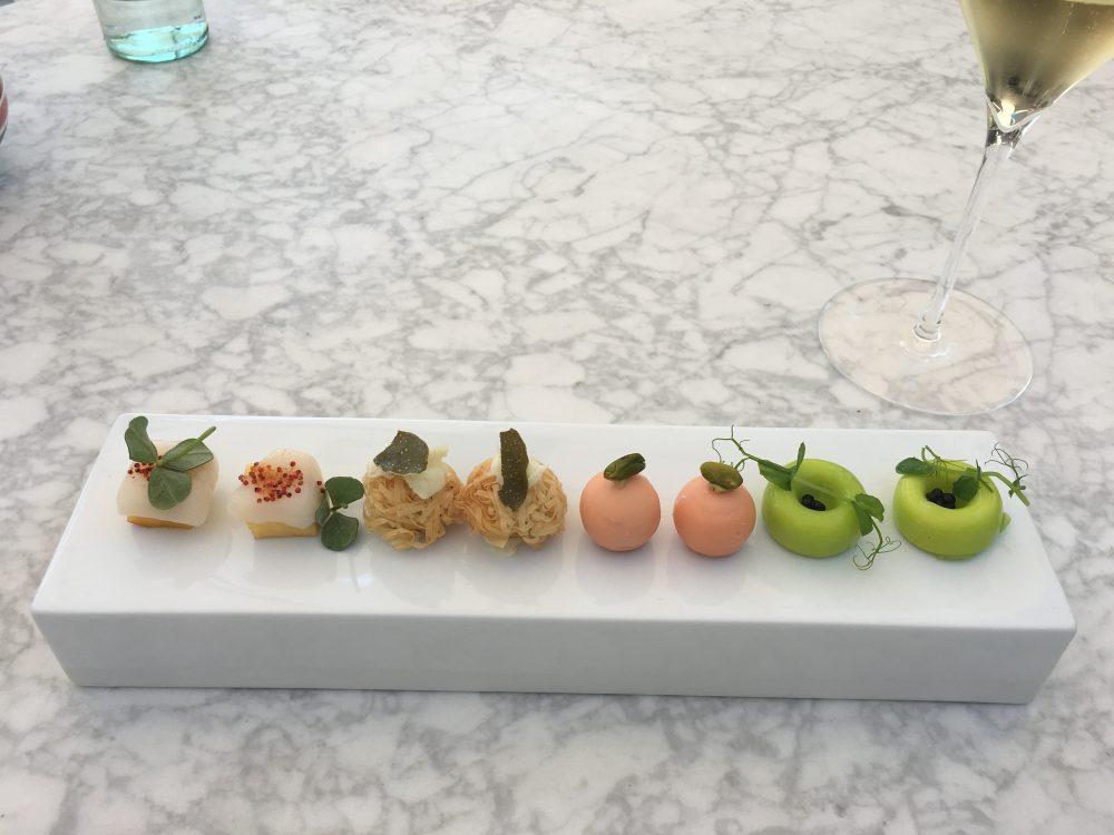 Felix Lo Basso, da dx panna cotta con piselli e perle di tartufo nero, pralina di prosciutto cotto e pistacchio, pastafilo e baccala', pesca con capasanta