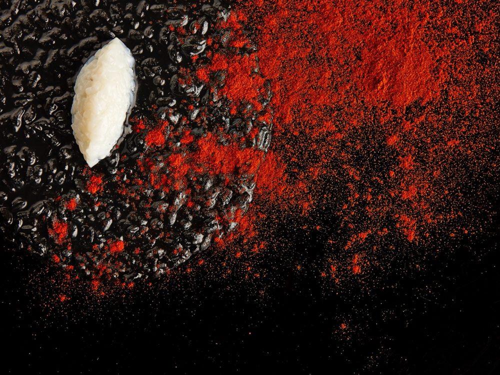 Risotto al nero, crudo di seppie e polvere di peperoni canditi