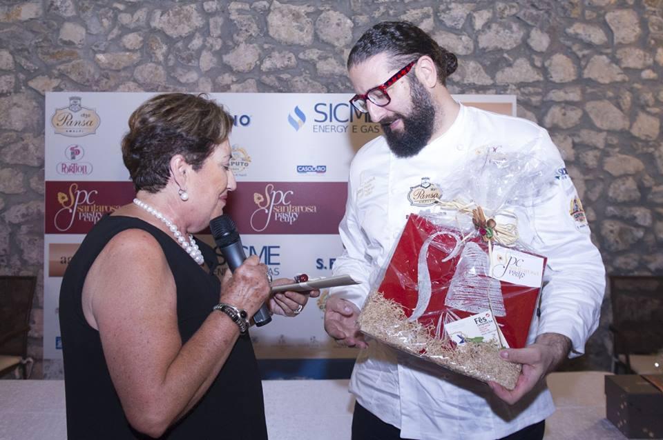 Carla Pansa, titolare dell'omonina pasticceria, consegna il premio al maestro Rinaldini