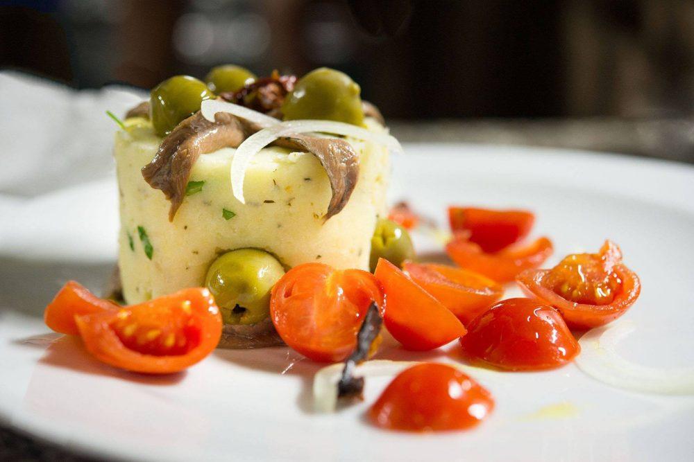 Bacco, patata scamazzata con olive, pomodori secchi, cipolla e acciughe - foto di Hostaria di Bacco