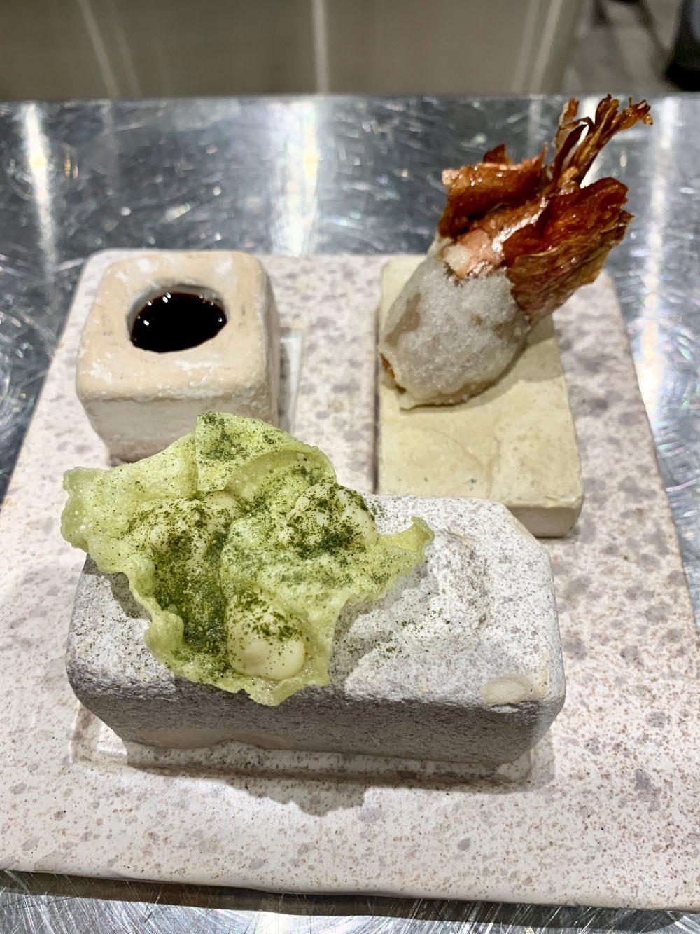 Due Camini - Scalogno cotto nel sale in tempura con vincotto, una chips di cicoria con crema di fave, oliva fritta con uva e un tartufino fatto di ricotta