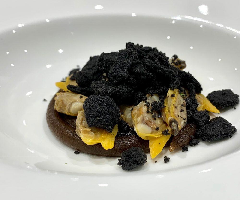 Due Camini - vongole su una base di patate all'aglio nero pane al nero di seppia, erbette di mare ed emulsione di burro acqua di vongole e alghe