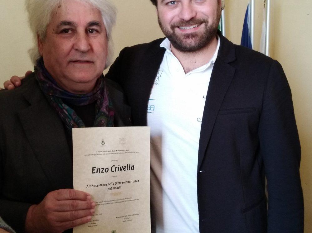 Enzo Crivella con la pergamena di Ambasciatore della Dieta Mediterranea nel Mondo consegnata dalle mani di Valerio Calabrese