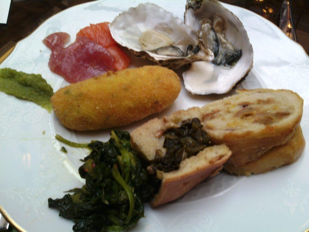Four Seasons, il piatto con i crudi di pesce, gli antipasti caldi e i piatti campani - crocche', casatiello, pizza di scarola, friarielli, ostriche, crudo di salmone e di tonno, ostriche