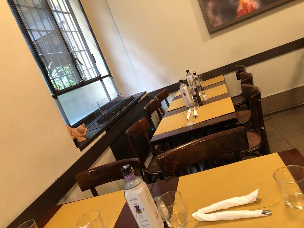 Trattoria da Pino, mezzogiorno meno uno, i tavoli ancora vuoti in attesa dei lavoratori