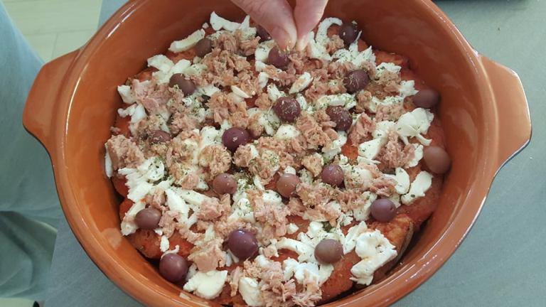 Pizza di pane raffermo, aggiunta di olive, tonno e origano